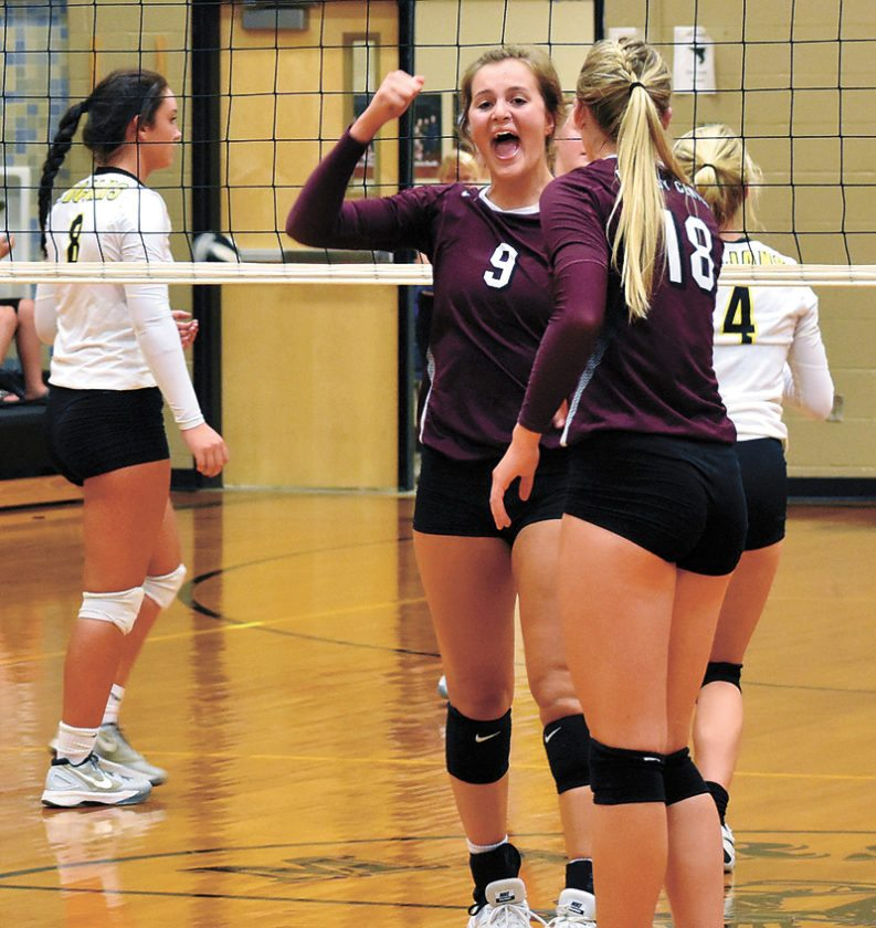 T-R PHOTO BY THORN COMPTON • Grundy Center junior Kylie Willis (9) celebrates with teammate Emerson Kracht (18) after scoring a point for the Spartans in their 3-0 sweep victory of West Marshall in State Center on Tuesday. Willis and Kracht each had season highs in kills in the win over the Trojans.
