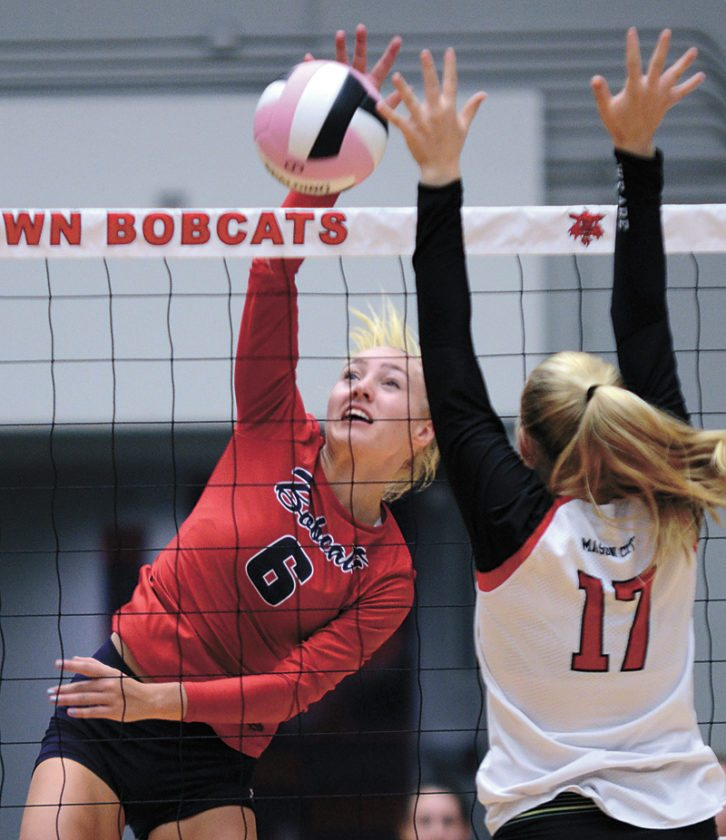 T-R PHOTO BY ROSS THEDE • Marshalltown senior Regan Mazour (6) swings for a kill around Mason City's Carly Seeck during the third set of Tuesday's CIML Iowa Conference match at the Roundhouse. Mazour had a team-high eight kills in the Bobcats' three-set sweep of the Mohawks.
