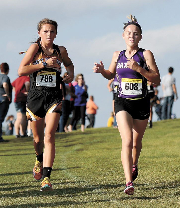 PHOTO BY TROY BANNING/DAILY FREEMAN JOURNAL • West Marshall's Avril Sinning, left, and Baxter's Brenna Thomson run side-by-side during Tuesday's West Marshall Trojan Cross Country Invitational at Lincoln Valley Golf Course near State Center. Sinning won medalist honors ahead of Thomson in a time of 21 minutes, 16 seconds.