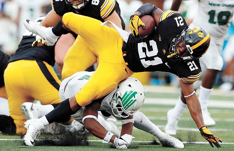 AP PHOTO • University of Iowa running back Ivory Kelly-Martin (21) is tackled by North Texas safety Khairi Muhammad during the second half of Saturday's college football game at Kinnick Stadium in Iowa City. Kelly-Martin had 11 carries for 74 yards as Iowa won 31-14.