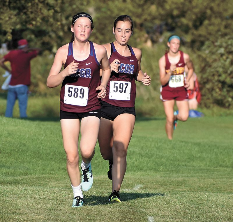 T-R PHOTO BY THORN COMPTON • Grundy Center/Gladbrook-Reinbeck harriers Lily Ehlers, left, and Reegan Zinkula run in tandem during the Spartan Invite on Thursday. Ehlers took fifth in the meet, while Zinkula finished in seventh.