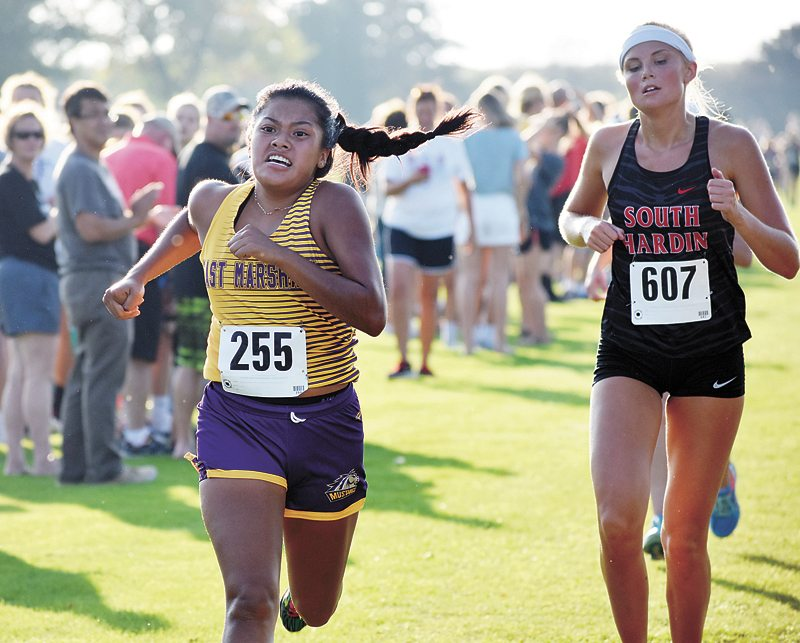 T-R PHOTO BY THORN COMPTON • East Marshall senior Cindy Liera, left, exerts her final effort to pass South Hardin senior Chloe Web as both girls approach the finish line in the Spartan Invite on Thursday.