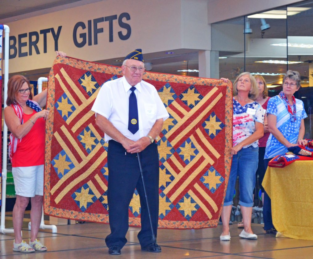 "Eighteen local veterans were honored for their service during Saturday's annual autumn Quilts of Valor ceremony, held at the Marshalltown Mall and presented by the Marshalltown-based Central Iowa Quilt Sew-ciety (CIQS). Pictured is veteran Ken Hoff being presented with his Quilt of Valor, entitled ""American Dream"