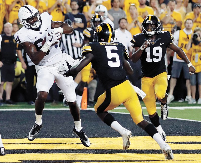 AP PHOTO • Penn State wide receiver Juwan Johnson, left, catches a touchdown pass as Iowa defensive backs Manny Rugamba (5) and Miles Taylor (19) give chase as time expires, lifting the Nittany Lions to a 21-19 win Saturday night at Kinnick Stadium in Iowa City.