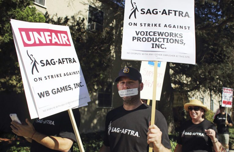 In this photo taken Nov. 3, 2016, video game voice actors picket outside Warner Bros. Studios in Burbank, Calif. The voice actors have agreed to end a nearly yearlong strike against several major gaming publishers. Their union, SAG-AFTRA, and a representative for the publishers said Monday, Sept. 25, 2017, that they reached a tentative agreement to end the strike on Saturday, Sept. 23. (AP Photo/Anthony McCartney)