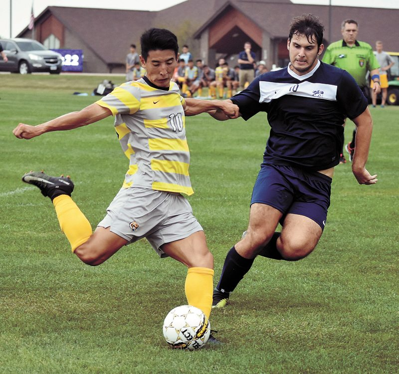 T-R PHOTO BY THORN COMPTON • Marshalltown Community College striker Kino Ryosuke, left, winds up for a shot in the Tigers' 8-1 win over the Mount Mercy junior varsity team at home Monday. Ryosuke had three goals and two assists for MCC in the win.