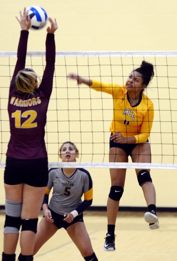 T-R PHOTO BY ROSS THEDE • Marshalltown Community College freshman outside hitter Jesenia Colbert (11) fires an attack off the block of Indian Hills CC's Laisa Telles Maeda (12) during the third set of Wednesday's ICCAC Division I match at the Student Activity Center.