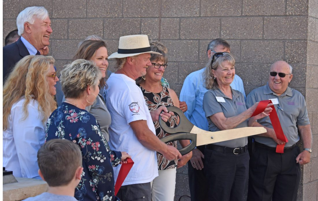 T-R PHOTO BY MIKE DONAHEY  Smiles and cheers abounded from Chamber of Commerce Ambassadors and others Thursday after a red ribbon was cut by Gallery Garden co-owners Jeff Mitchell (holding scissors) and Barb Hagstrand, standing to Mitchell's right. Situated next to the Kibbey Building, a water garden, with rows and rows of green plants adorn the building's east wall just below a giant metal butterfly.