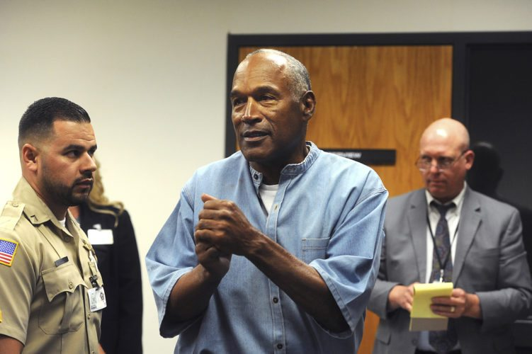 FILE - In this July 20, 2017 file photo, former NFL football star O.J. Simpson reacts after learning he was granted parole at Lovelock Correctional Center in Lovelock, Nev. Nevada's parole board says it didn't consider O.J. Simpson's 1989 conviction for misdemeanor spousal abuse when it granted him parole in July because it wasn't listed in the federal clearinghouse of FBI crime data.   (Jason Bean/The Reno Gazette-Journal via AP, Pool, File)
