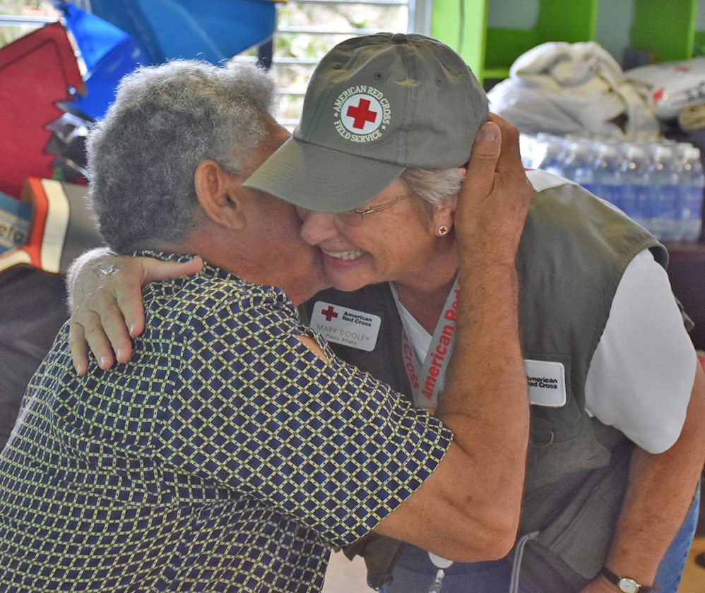 A Puerto Rican survivor of Hurricane Irma and Hurricane Maria, left, gives American Red Cross volunteer Mary Dooley of Albion a hug recently at a Red Cross shelter. Dooley was stationed 10 days on the island following both hurricanes providing aid and comfort.