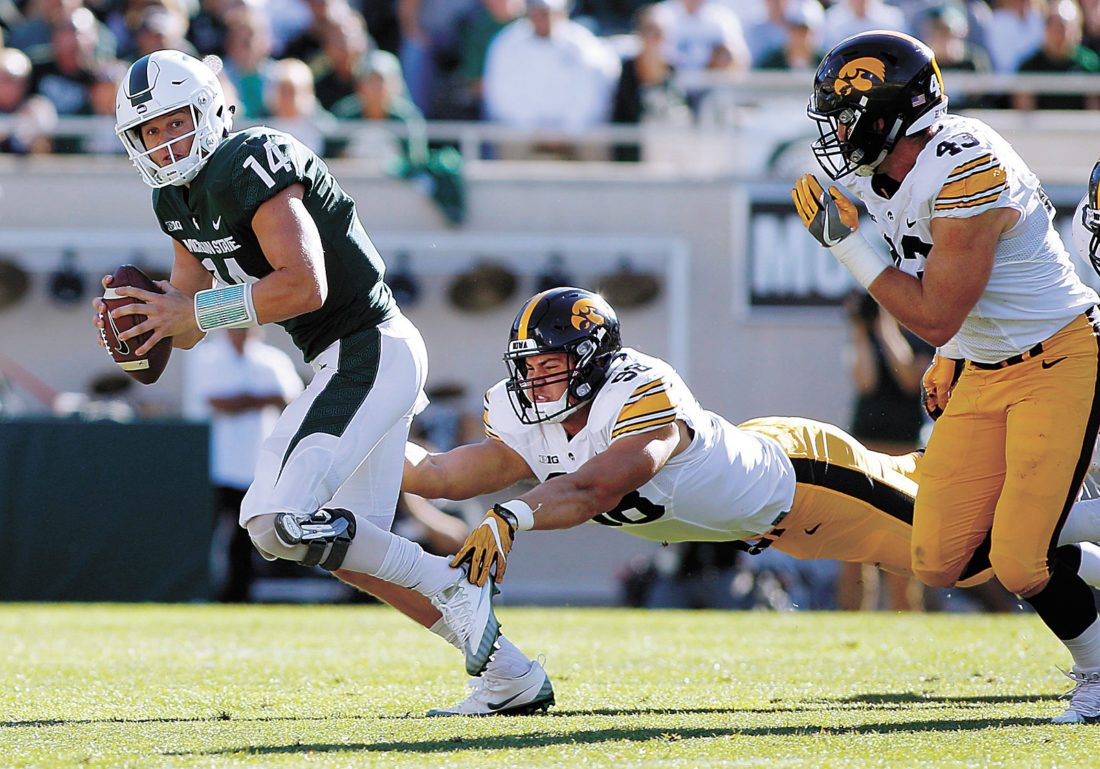 AP PHOTO • Iowa's Anthony Nelson, center, trips up Michigan State quarterback Brian Lewerke, left, as Iowa's Josey Jewell, right, pursues during the first half of the Spartans' win over the Hawkeyes on Saturday in East Lansing, Mich.
