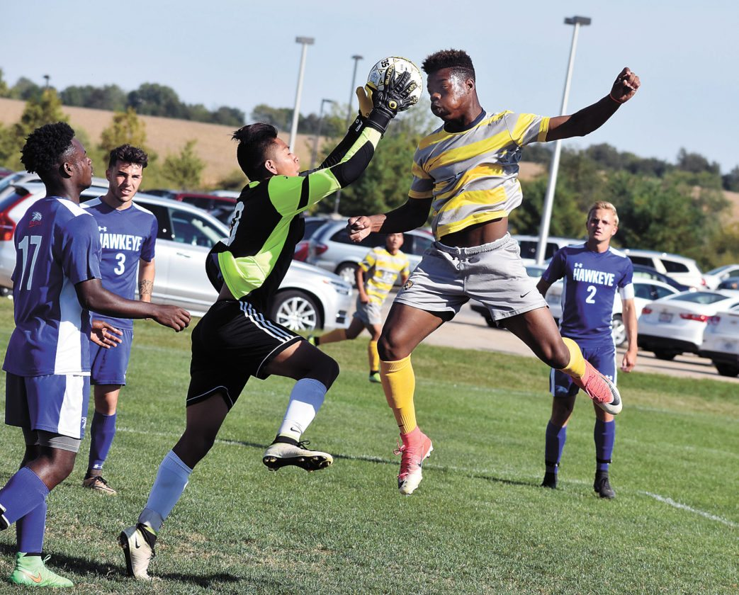 T-R PHOTO BY THORN COMPTON • Marshalltown Community College striker David Kromah, right, goes up for a header off a corner kick while Hawkeye Community College goalkeeper Vladimir Gonzalez, left, grabs the ball during the Tigers' 5-0 rout of the RedTails at home on Saturday.