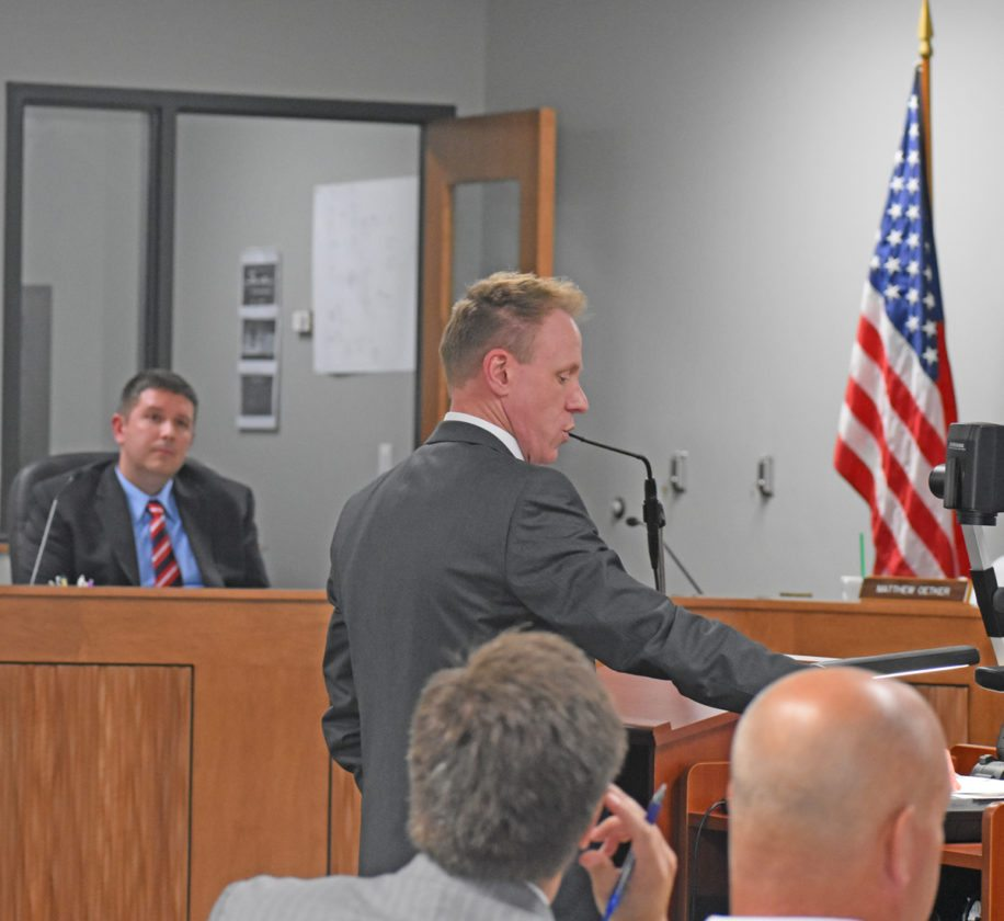 T-R PHOTO By MIKE DONAHEY Marshalltown Public Works Director Justin Nickel, far left, looks on while Attorney Patrick O'Connell, standing, speaks before State of Iowa City Development Board members not pictured Wednesday in city council chambers. Also looking on are Attorney Michael Marquess, seated center, and petioner Monte Eaton, seated, lower right. City Development Board members heard arguments from Marquess, representing Eaton and Jim Gruening to sever their properties from the city. O'Connell, representing the city, contested their request be denied.