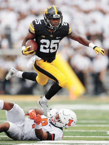 AP PHOTO • Iowa running back Akrum Wadley (25) hurdles Illinois linebacker Dele Harding during the first half of a Big Ten Conference football game Saturday in Iowa City.