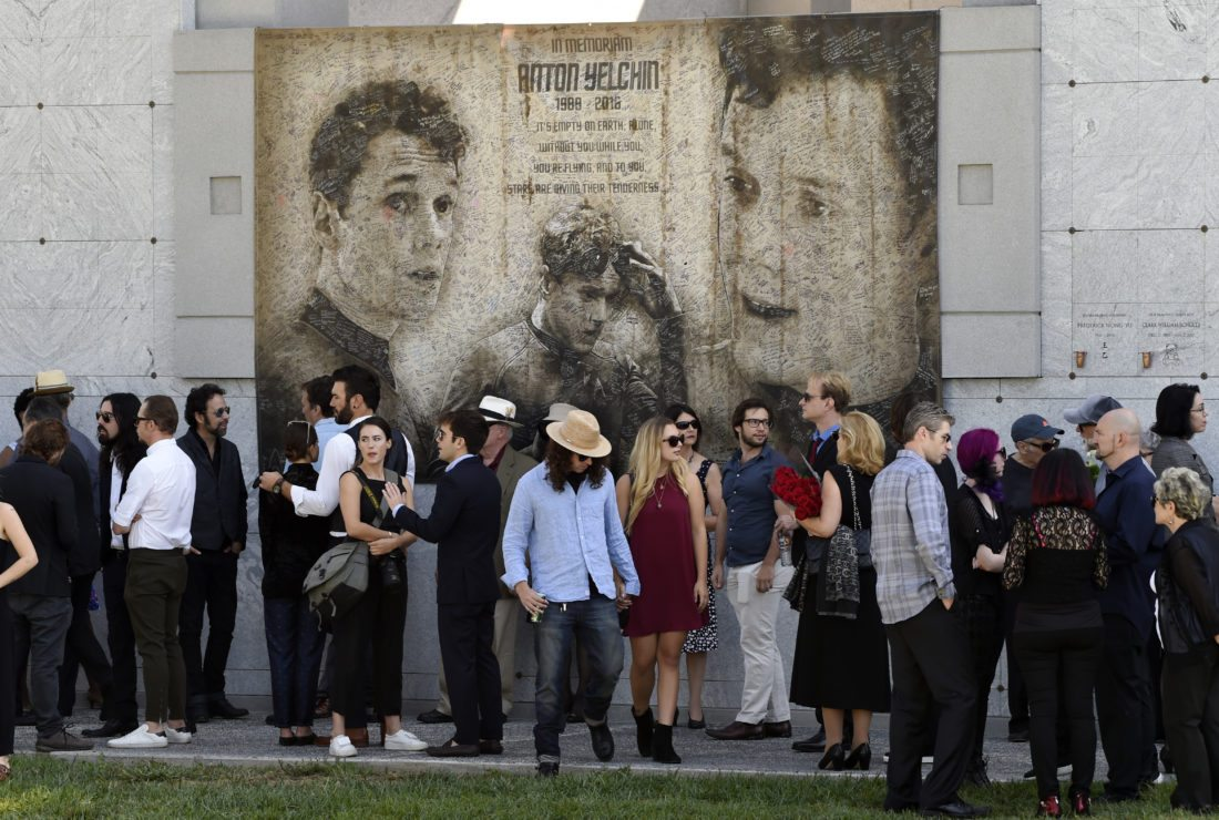 """Guests gather beneath a mural of the late actor Anton Yelchin created by fans at a """"Star Trek"""" convention, during a life celebration and statue unveiling for Yelchin at Hollywood Forever Cemetery on Sunday, Oct. 8, 2017, in Los Angeles. (Photo by Chris Pizzello/Invision/AP)"""