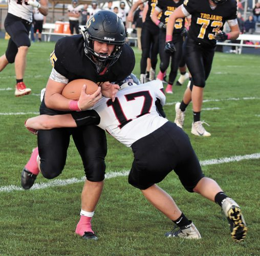 T-R PHOTO BY THORN COMPTON • West Marshall running back Alex Dickey powers through a tackle by South Hardin's Tyler Briggs during the Trojans' 48-0 shellacking of the Tigers in State Center on Monday night.