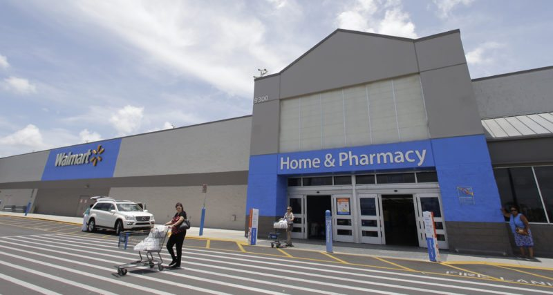 In this Thursday, June 1, 2017, photo, customers walk out of a Walmart store in Hialeah Gardens, Fla. Walmart is expected to provide an update about its expansion plans and issue an outlook for revenue and earnings at its annual shareholder meeting, Tuesday, Oct. 10, 2017. (AP Photo/Alan Diaz)