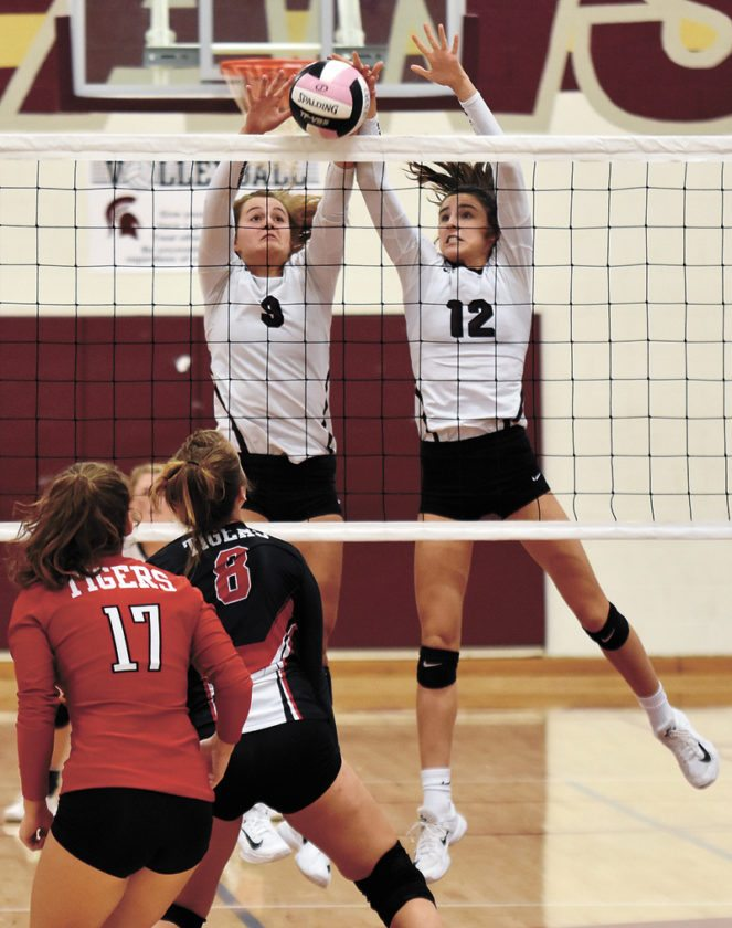 T-R PHOTO BY THORN COMPTON • Grundy Center's Kylie Willis (9) and Hailey Wallis (12) block a shot from South Hardin's Chloe Edgerton (8) during the Spartans' 3-0 sweep of the Tigers on Tuesday. With the win, Grundy Center clinched its ninth-straight NICL West Division championship.