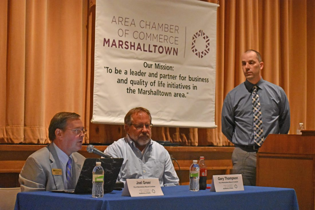 T-R PHOTO BY MIKE DONAHEY  Second ward councilor and mayoral candidate Joel Greer, left, makes remarks at the Marshalltown Area Chamber of Commerce-sponsored city council candidate forum Wednesday night at the Fisher Community Center. Looking on is mayoral candidate Gary Thompson, center, and forum moderator Todd Steinkamp, right. Steinkamp is a Chamber board member and General Manager of KFJB-KXIA-FM Radio. The event was open to the public and free-of-charge.