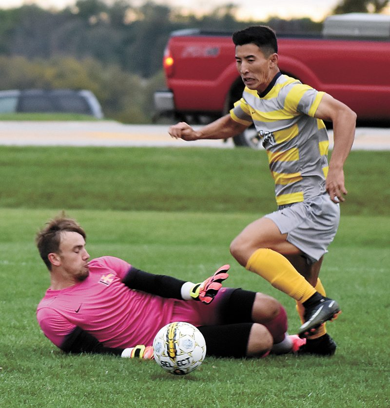 T-R PHOTO BY THORN COMPTON • Marshalltown Community College striker Kino Ryosuke, right, slips a pass to a teammate while Indian Hills goalkeeper Ross Dalton challenges him during the Tigers' 2-1 victory over the Warriors on Wednesday. Ryosuke's pass assisted Roger De la Villa on the game-winning goal moments after.