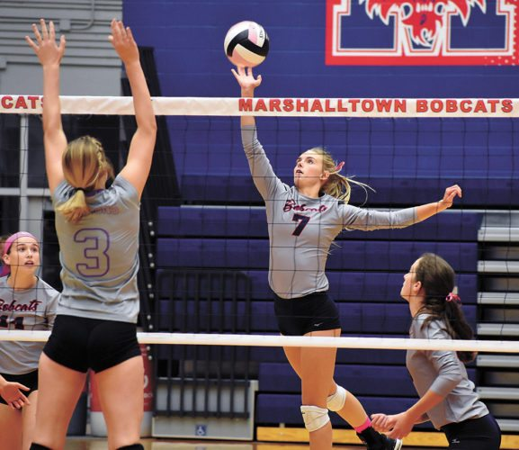T-R PHOTO BY THORN COMPTON • Marshalltown senior Ciara Feldman (7) tips the ball over the net towards Johnston's Maddie Mock during the Bobcats' three-set sweep of the Dragons on Thursday.