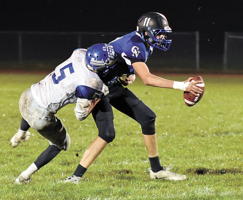 T-R PHOTO BY THORN COMPTON • Colo-NESCO passer Sean Cutler, right, is sacked by Moravia's Griffin Cosgrove (5) during the fourth quarter of the Royals' 30-22 loss to the Mohawks in Colo on Friday night.