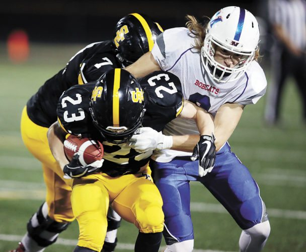 T-R PHOTO BY REESE STRICKLAND • Marshalltown's Blake Linsenmeyer, right, brings down Southeast Polk's Nathan Marchand (23) during the host Rams' 52-0 shutout of the Bobcats on Friday night at Rams Stadium in Pleasant Hill.