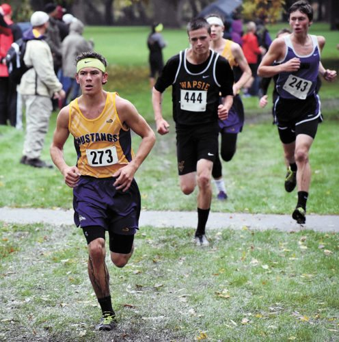 T-R PHOTO BY THORN COMPTON • East Marshall junior Cam Hungerford, left, leads a pack of runners during the North Iowa Cedar League meet in a rainy Reinbeck on Saturday.