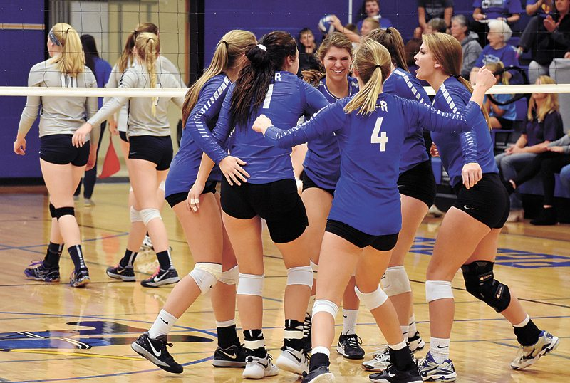 T-R PHOTO BY THORN COMPTON • Members of the Gladbrook-Reinbeck volleyball team gather to celebrate after scoring a point in the first set of the Rebels' three-set sweep of AGWSR in the first round of the regional playoffs on Tuesday.