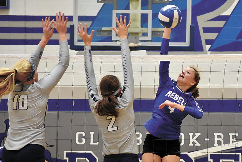 T-R PHOTO BY THORN COMPTON • Gladbrook-Reinbeck freshman Saari Kuehl (4) goes up for a kill against AGWSR defenders Taryan Barrick (10) and Mandi Willems (2) during the third set of the Rebels sweep of the Cougars on Tuesday.