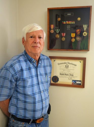"T-R PHOTO BY CHUCK FRIEND Marshalltown veteran Robert ""Bob"" Hibbs stands by his honorable discharge certificate and some of the medals and ribbons earned while serving in the U.S. Army during the Vietnam era."