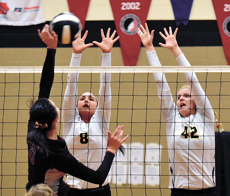 T-R PHOTO BY THORN COMPTON • West Marshall defenders Grace Porter (8) and Teresa Disney (42) go up for a block against PCM's Regan Olson during the Trojans' three-set sweep of the Mustangs on Wednesday in State Center.