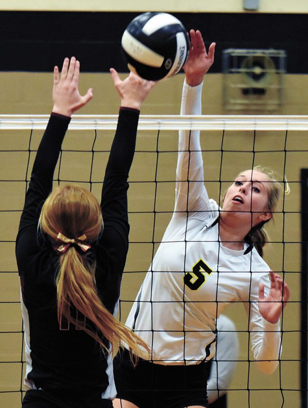 T-R PHOTO BY THORN COMPTON • West Marshall senior Lexi Keigan (5) goes up against a PCM defender for one of her team-leading 13 kills in the Trojans' 3-0 sweep of the Mustangs in the first round of the Class 3A Region 6 tournament in State Center on Wednesday.