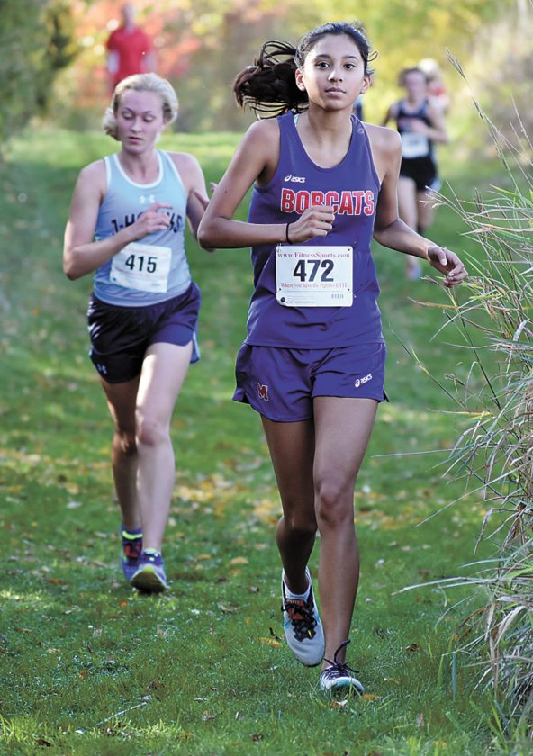 T-R PHOTO BY THORN COMPTON • Marshalltown's Mia Barajas, right, heads into the last third of the cross country course at Marshalltown Community College on Thursday while competing in the Class 4A state-qualifying meet.