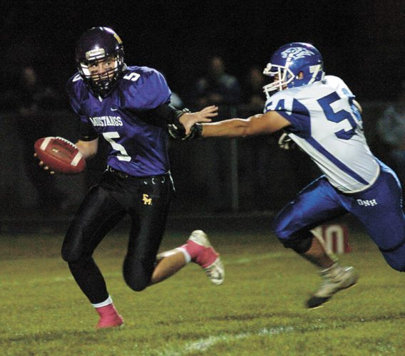 T-R PHOTO BY  ROSS THEDE • East Marshall senior quarterback Tyler DeBondt, left, scrambles out of the grasp of Dike-New Hartford defender Daniel Graves during the first quarter of their Class 2A District 3 football game Friday night in Le Grand. The Wolverines won 42-20.