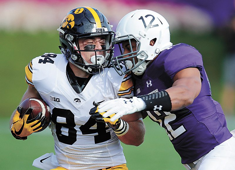 AP PHOTO • Iowa's Nick Easley, left, is tackled by Northwestern's Alonzo Mayo during the first half of a Big Ten Conference football game Saturday in Evanston, Ill.