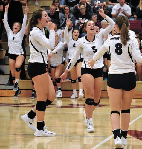 T-R PHOTO BY THORN COMPTON • Grundy Center players Kylie Willis, left, Hannah Stahl (5) and Sydney Mathews (8) celebrate after the Spartans completed their sweep of Hudson on Monday night in Class 2A Region 5 semifinals.