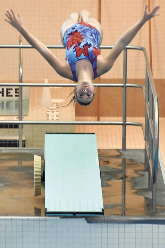 T-R PHOTO BY THORN COMPTON • Marshalltown junior Sami Trowbridge reaches the apex of her dive during the early going of the regional diving meet at Grinnell College on Thursday. Sami and her sister Alli both earned state qualifications with their performances at the meet.