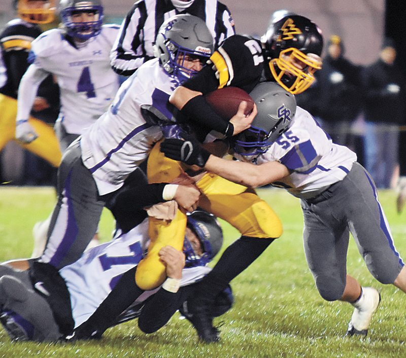 T-R PHOTO BY THORN COMPTON • Gladbrook-Reinbeck defenders Kyle Koppen (55), Gage Murty, left, Bronson Wrage, below, team up to gang-tackle Wapsie Valley quarterback Tanner Sauerbrei (21) after a gain during Friday's Class A state football playoff game in Fairbank.