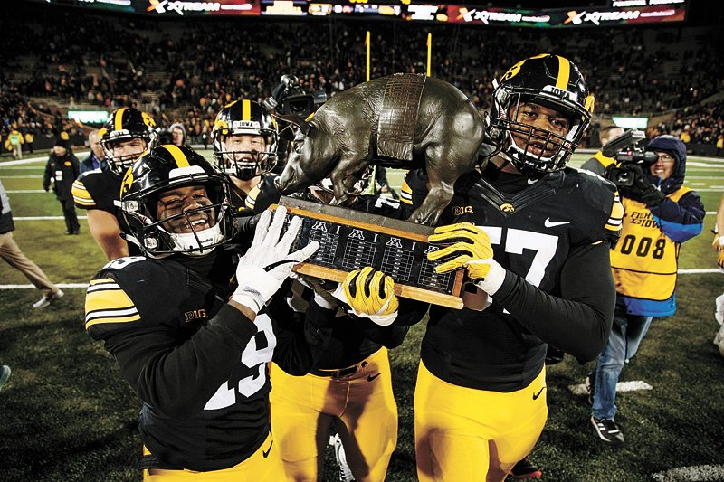 AP PHOTO • Iowa's Miles Taylor (19) and Iowa's Chauncey Golston (57) carry the Floyd of Rosedale trophy off the field after Iowa defeated Minnesota 17-10 during a Big Ten Conference football game Saturday at Kinnick Stadium in Iowa City.