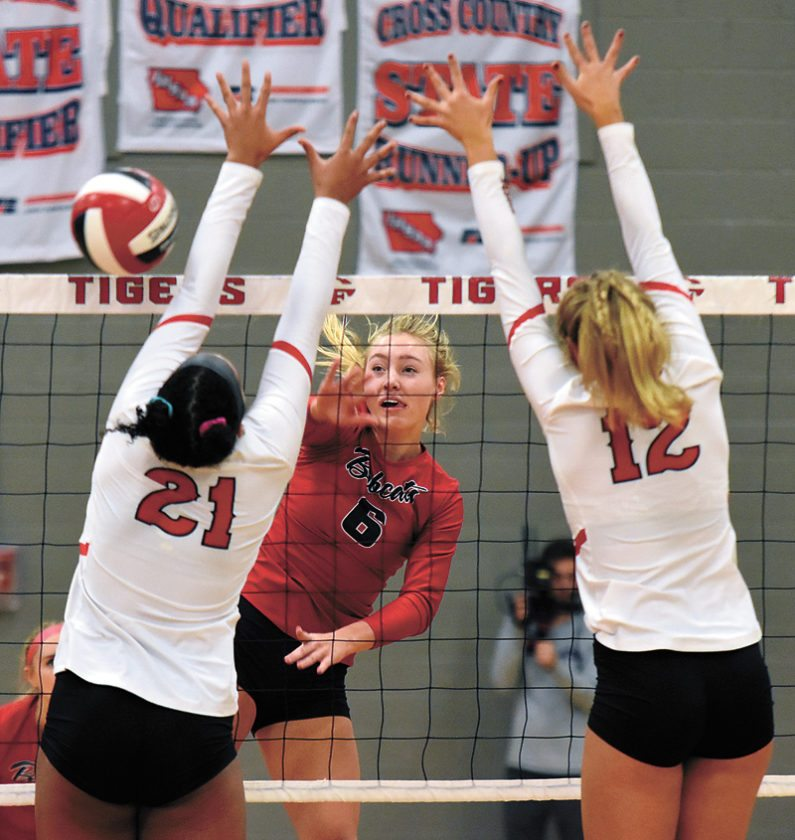 T-R PHOTO BY THORN COMPTON • Marshalltown senior Regan Mazour (6) records a kill while Akacia Brown (21) and Claire Gerdes (12) from Cedar Falls attempt to block the ball during the Tigers' three-set sweep of the Bobcats in the regional finals on Monday.