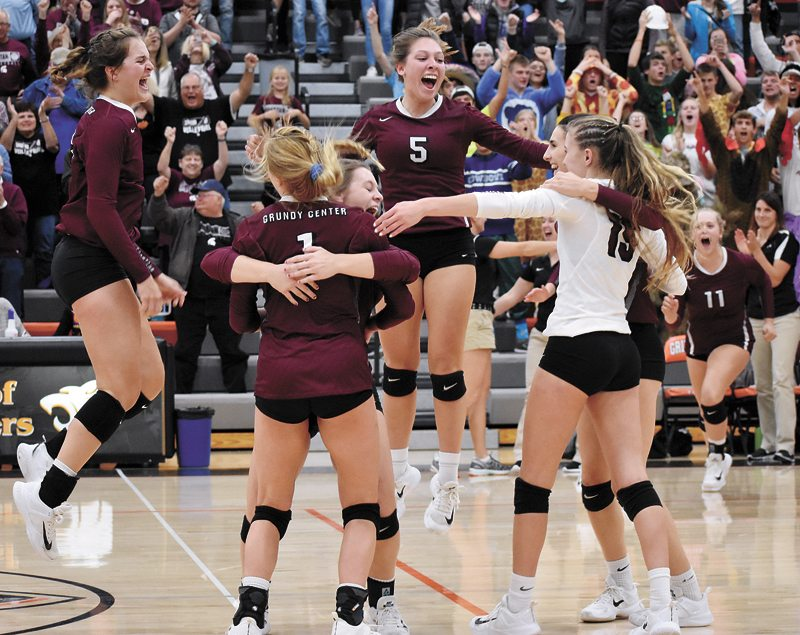 T-R PHOTO BY THORN COMPTON • Grundy Center players Kylie Willis, left, and Hannah Stahl (5) take to the air while gathering to celebrate with their teammates after the Spartans secured their spot at state with a 3-1 win over Pella Christian on Tuesday night.