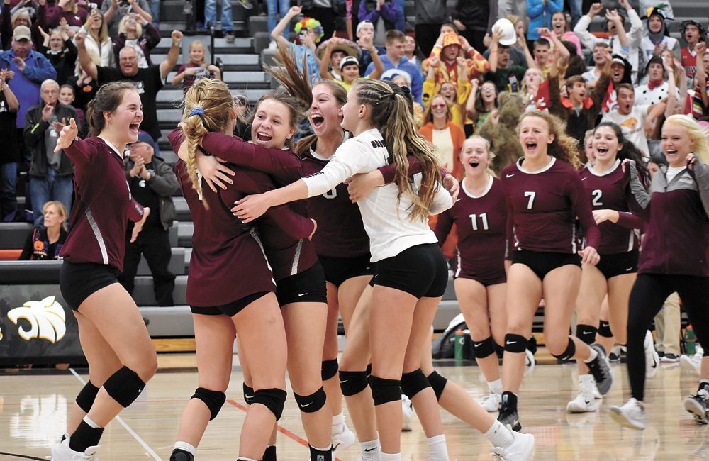T-R PHOTO BY THORN COMPTON • The Grundy Center volleyball teams swarm together after scoring the final point in the fourth set to complete the 3-1 victory over Pella Christian and earn a second-straight trip to the state tournament.