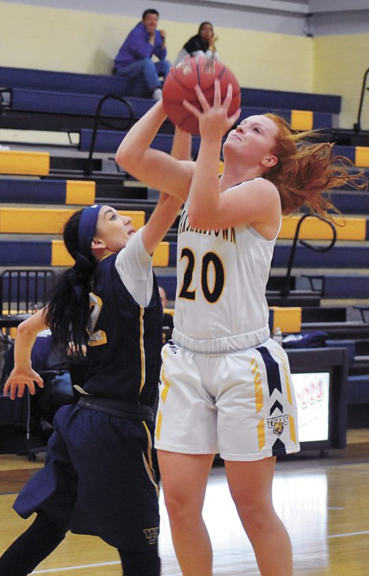 T-R PHOTO BY THORN COMPTON • Marshalltown Community College sophomore Alyssa Roth (20) puts up a shot while William Penn senior Sydney Thompson attempts to block it during the Statesmen's 68-46 win over the Tigers on Wednesday.