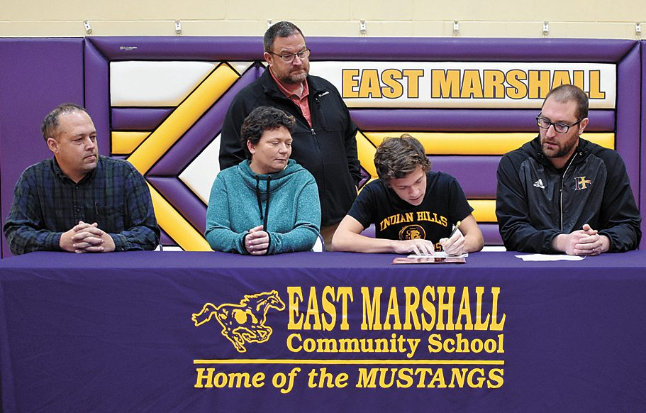 T-R PHOTO BY THORN COMPTON • East Marshall senior Seth Kilborn, second from right, signs his letter of intent to attend Indian Hills Community College on a scholarship on Thursday. Kilborn is joined at the table his father Scott Kilborn, left, mother Cari Glackl, second from left, high school coach Trent Taylor, center, and Indian Hills coach Scott Barnes, right.