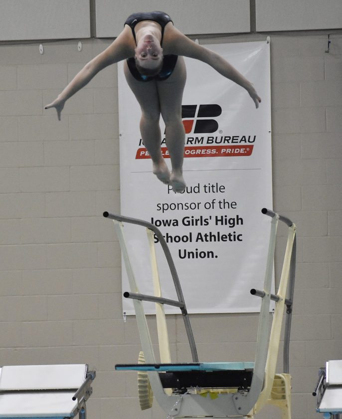 T-R PHOTO BY THORN COMPTON • Marshalltown junior Alli Trowbridge arcs backwards during one of her early dives on her way to placing 11th at the Iowa Girls' High School State Diving Championships at the Marshalltown YMCA/YWCA on Friday night.