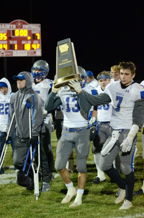 T-R PHOTO BY ROSS THEDE • Gladbrook-Reinbeck players Walker Thede (7) and Matt Johannsen (13) walk off the field holding the state participant trophy after the Rebels 35-7 loss to St. Ansgar in the Class A quarterfinals on Friday night.