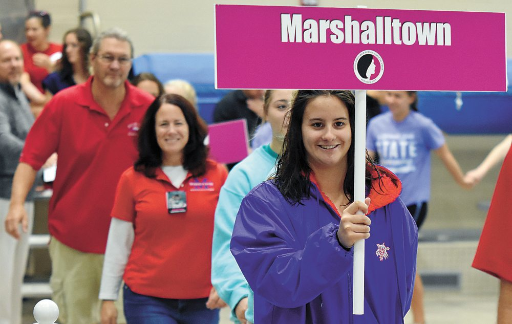 T-R PHOTO BY THORN COMPTON • Marshalltown senior Zoe Beals, right, leads the Marshalltown procession during the parade of athletes before competition during the second day of the Iowa Girls' High School State Swimming and Diving Championships on Saturday. Beals finished 23rd in the 50-yard freestyle, the only Bobcat swimmer to compete on Saturday.