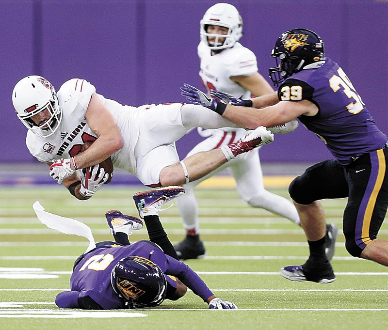 AP PHOTO • Northern Iowa's Malcolm Washington and Duncan Ferch, right, tackle South Dakota's Brett Samson during during a Missouri Valley Football Conference game Saturday at the UNI-Dome in Cedar Falls.