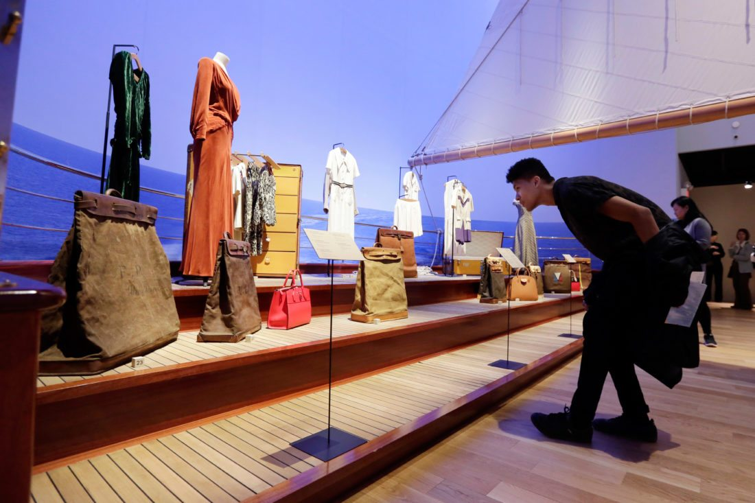 "A visitor views items in ""The Rise of Yachting"" section, part of the ""Volez, Voguez, Voyagez,"" Louis Vuitton exhibit, in the former American Stock Exchange building, in New York Financial District, Monday, Nov. 6, 2017. The luxury French brand, founded in the mid-19th century, is telling its story with a free, museum-like exhibition of artifacts, products and immersive displays. The exhibition is on view at the American Stock Exchange Building in Lower Manhattan until Jan. 7. (AP Photo/Richard Drew)"
